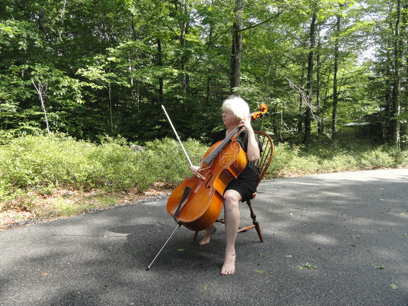 Female cellist. Female cellist performing a classical solo outside royalty free stock photos