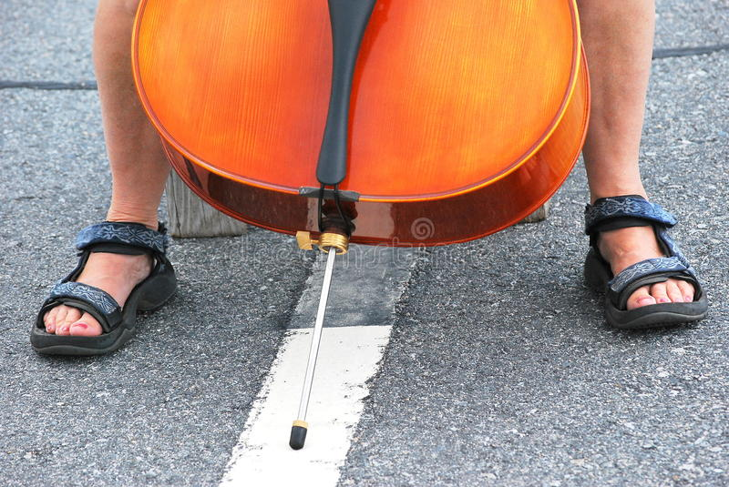 Female cellist performing. Female cellist performing in concert outdoors royalty free stock photo