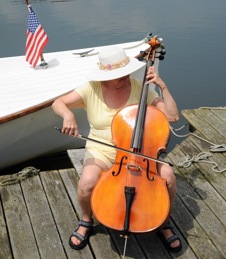 Female cellist. Female cellist performing on the lake outside stock photo