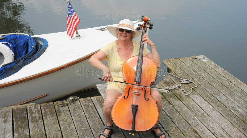 Female cellist. Female cellist performing on the lake outside royalty free stock photography