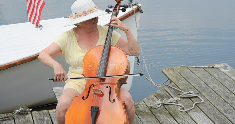 Female cellist. Female cellist performing on the lake outside royalty free stock image