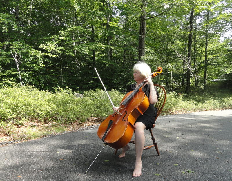 Female cellist performing. Mature female cellist performing a classical solo outdoors royalty free stock photography