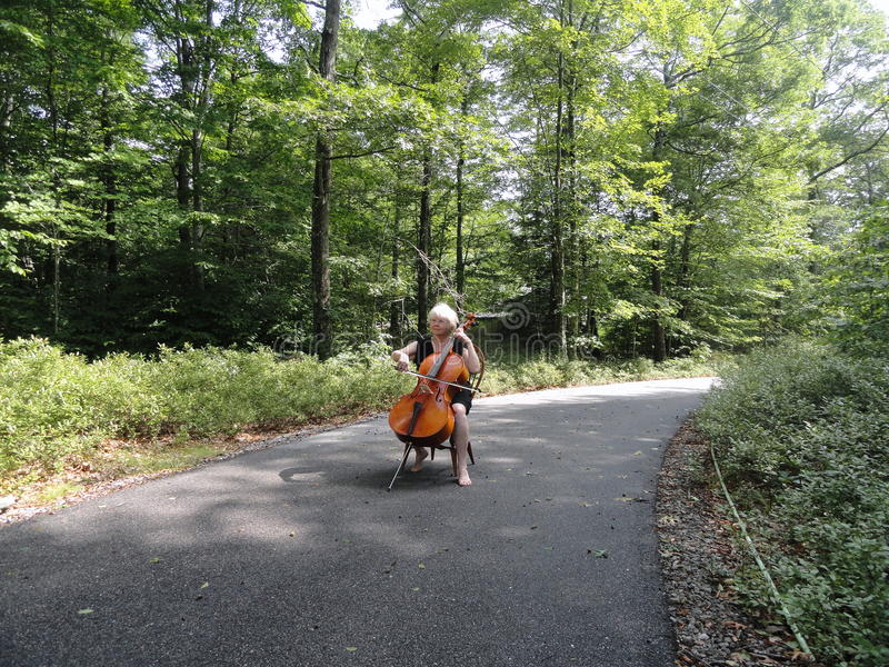 Female cellist performing. Mature female cellist performing a classical solo outdoors stock images
