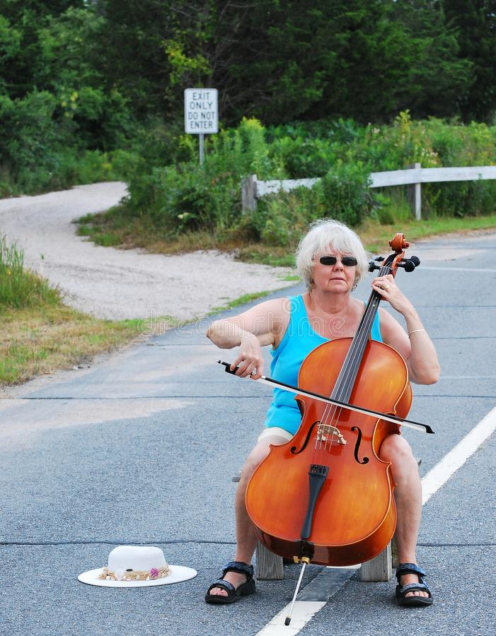 Female cellist performing. Mature female cellist performing a solo concert on the street outdoors royalty free stock images