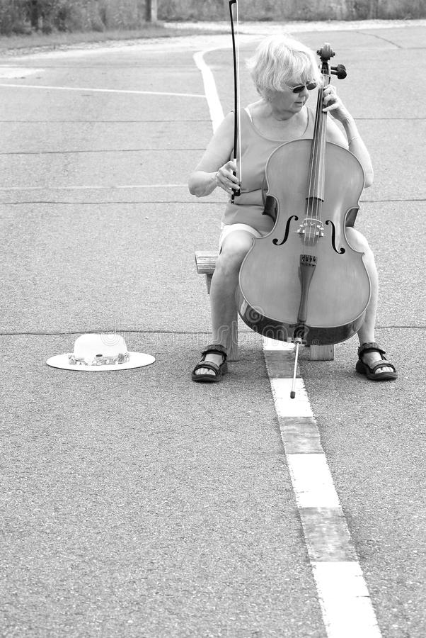 Female cellist performing. Mature female cellist performing a solo concert on the street outdoors stock photo