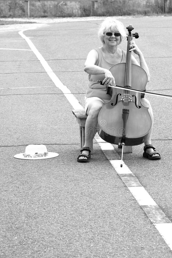 Female cellist performing. Mature female cellist performing a solo concert on the street outdoors stock photography