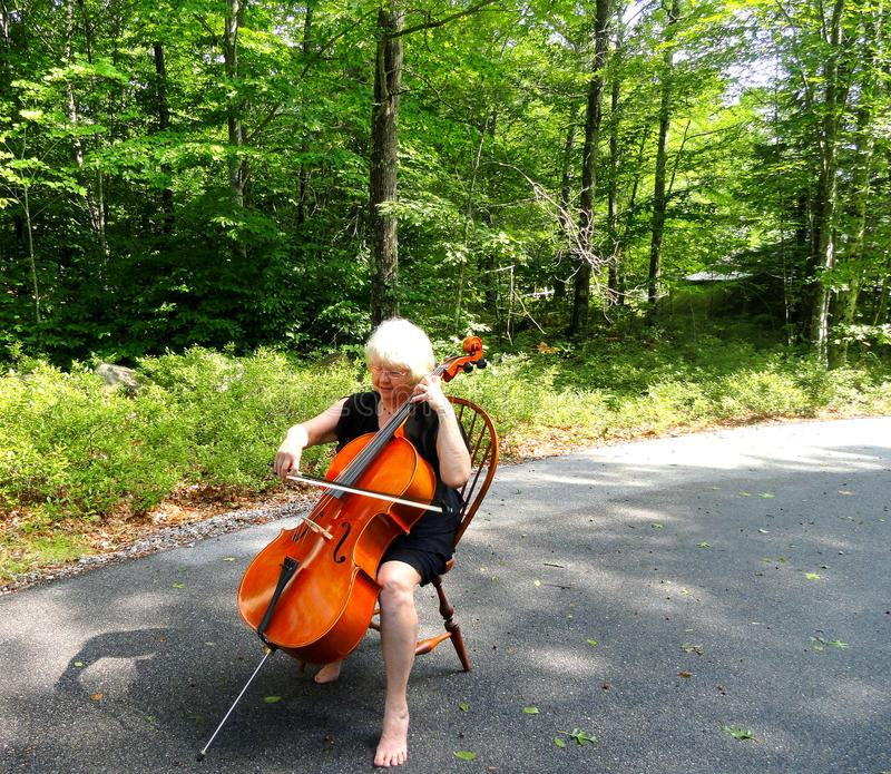 Female cellist performing. Mature female senior cellist performing on her instrument outdoors royalty free stock photos