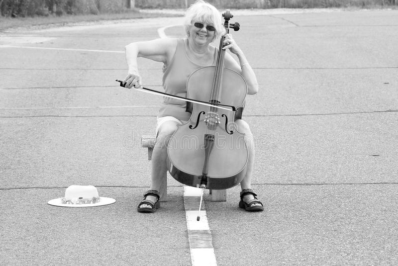Female cellist performing. Mature female cellist performing a solo concert on the street outdoors royalty free stock photos