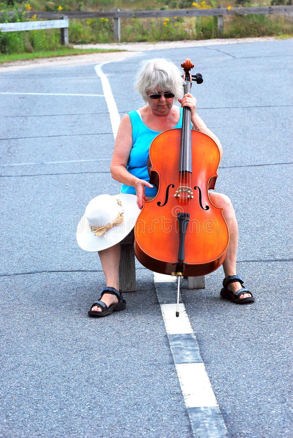 Female cellist performing. Mature female cellist performing in the streets outdoors stock images