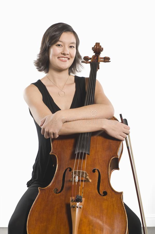 Female Cellist Sits With Arms Folded Across Cello. Portrait of a happy female cellist sits with arms folded across cello royalty free stock image