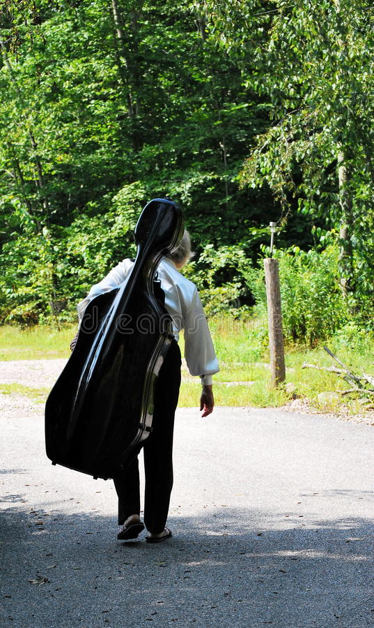 Female cellist. Female cellist walking home from music college stock photo