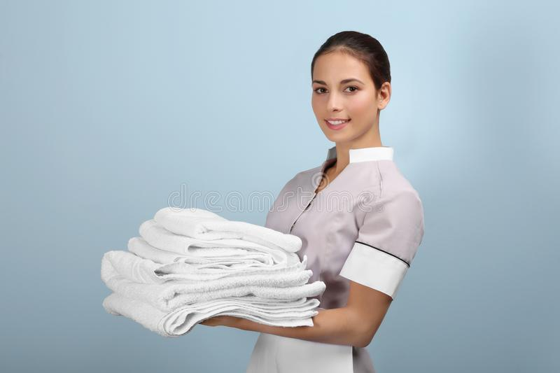 Female chambermaid holding clean white folded towels royalty free stock photography