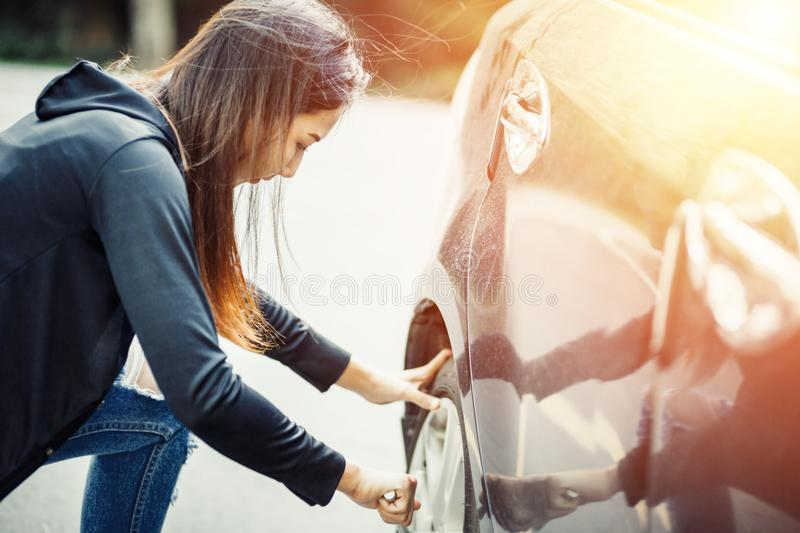 Female changing tire with wheel wrench with sun light stock photography