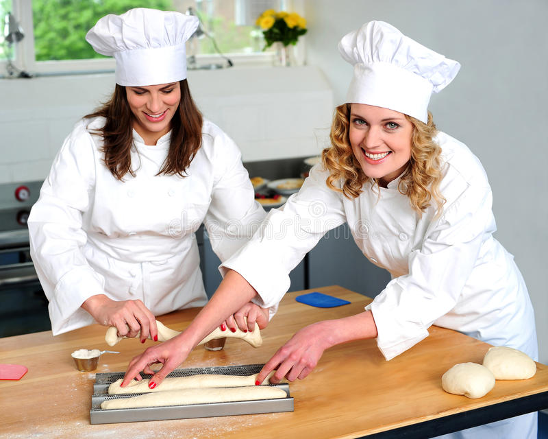 Female Chef Arranging Prepared Dough Stock Image