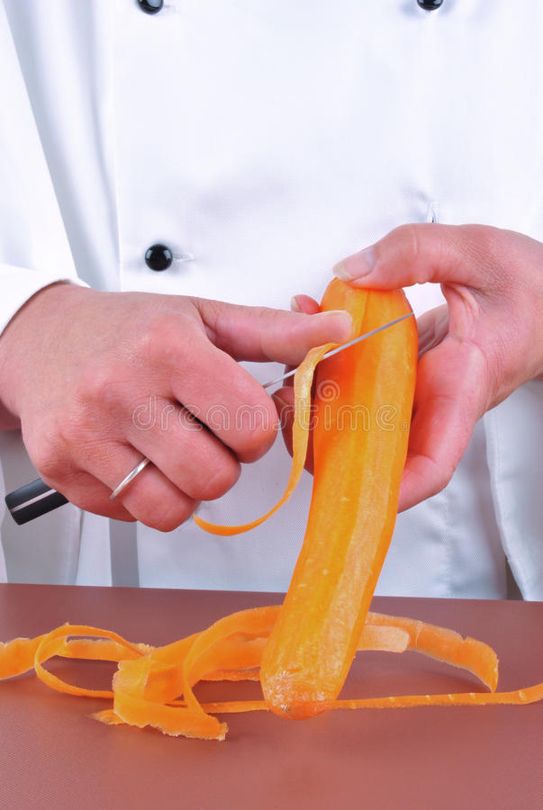 Female chef cuts a carrot with a kitchen knife stock photography