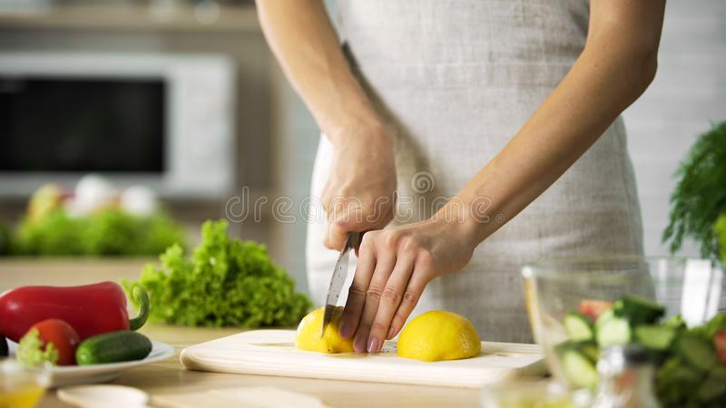 Female chef cutting lemon with sharp knife for lunch preparing, cooking tips stock image