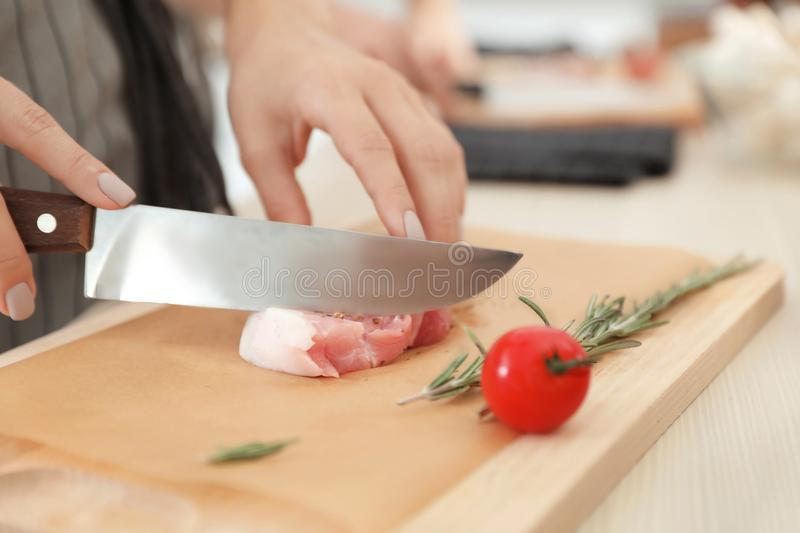 Female chef cutting meat on wooden board at table. Closeup stock photos