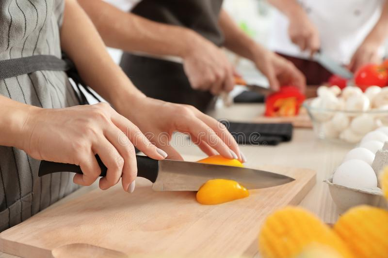 Female chef cutting paprika on wooden board stock images