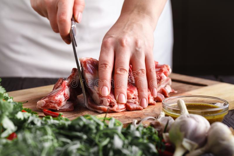 Female Chef cutting raw lamb meat on wooden board prepared for cooking royalty free stock images