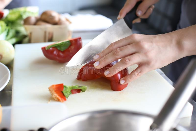 Female chef cutting vegetables in restaurant kitchen, closeup stock photos