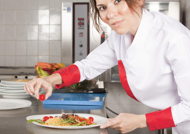Female chef in kitchen decorating royalty free stock photo