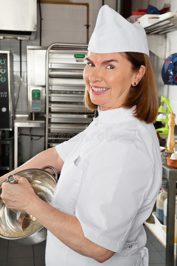 Female Chef Mixing Egg In Container royalty free stock images