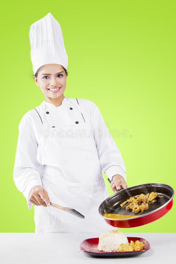 Female chef pouring tripe soup into a plate. Happy female chef pouring tripe soup into a plate with white rice while standing in the studio stock photo