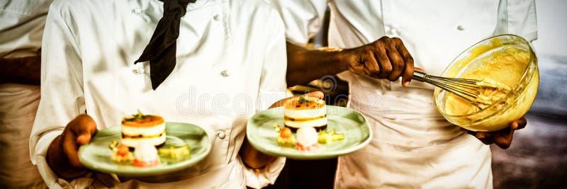 Female chef presenting dessert plates stock images