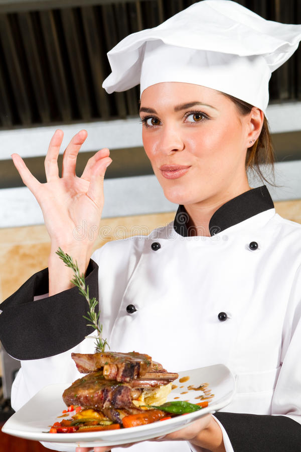 Female chef presenting food. Young beautiful female chef presenting food in kitchen stock images