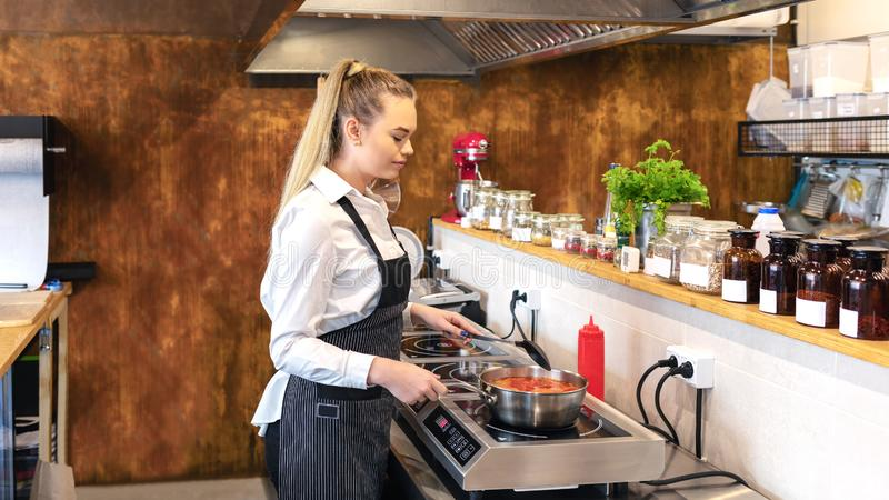 Female chef in restaurant or new small business kitchen cooking delicious food on modern electric stove stock photography