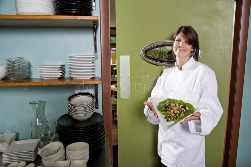 Female chef in restaurant with salad plate