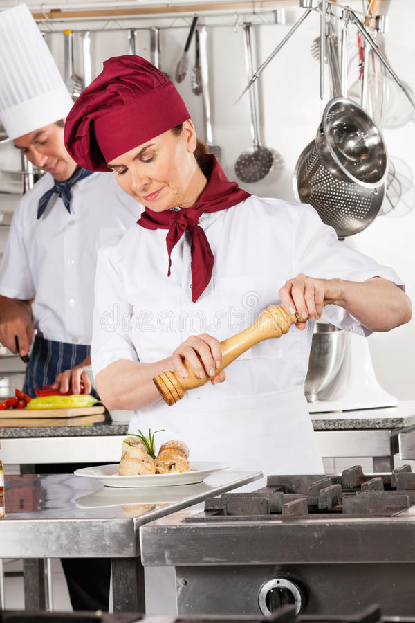 Female Chef Seasoning Salmon Roll royalty free stock images