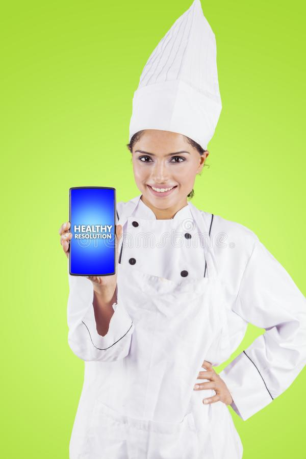 Female chef shows healthy resolution text on studio. Young female chef showing healthy resolution text on a mobile phone while standing in the studio royalty free stock photo