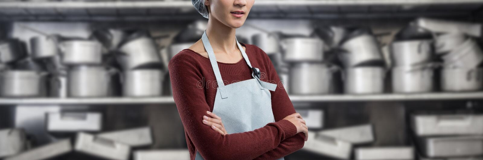 Composite image of female chef standing with arms crossed. Female chef standing with arms crossed against shelf full of pots royalty free stock photos