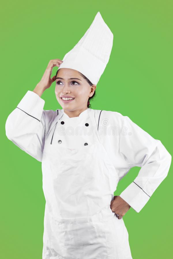 Female chef thinking something in the studio. Portrait of young female chef thinking something while scratching her head in the studio with green screen stock photo