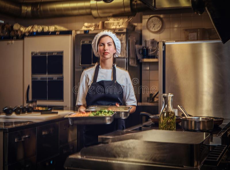Female chef wearing a uniform holding a container with chopped vegetables at restaurant`s kitchen. stock photos