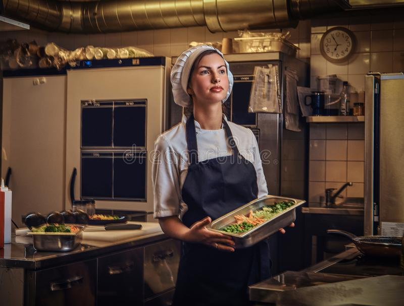 Female chef wearing a uniform holding a container with chopped vegetables at restaurant`s kitchen. stock images