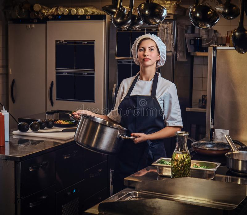 Female chef wearing a uniform holding a pan at restaurant`s kitchen. royalty free stock photography