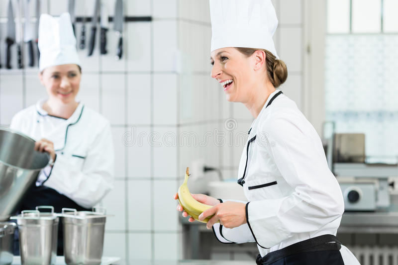 Female chefs in commercial kitchen wearing white uniforms. Two female chefs in gastronomic kitchen wearing white cooking uniforms stock image