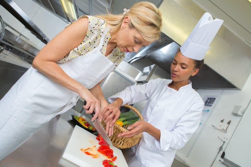 Female chefs garnishing plate in kitchen stock image