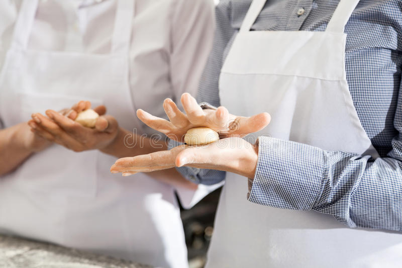 Female Chefs Making Pasta Dough Balls In Kitchen. Midsection of female chefs making pasta dough balls in commercial kitchen stock photos