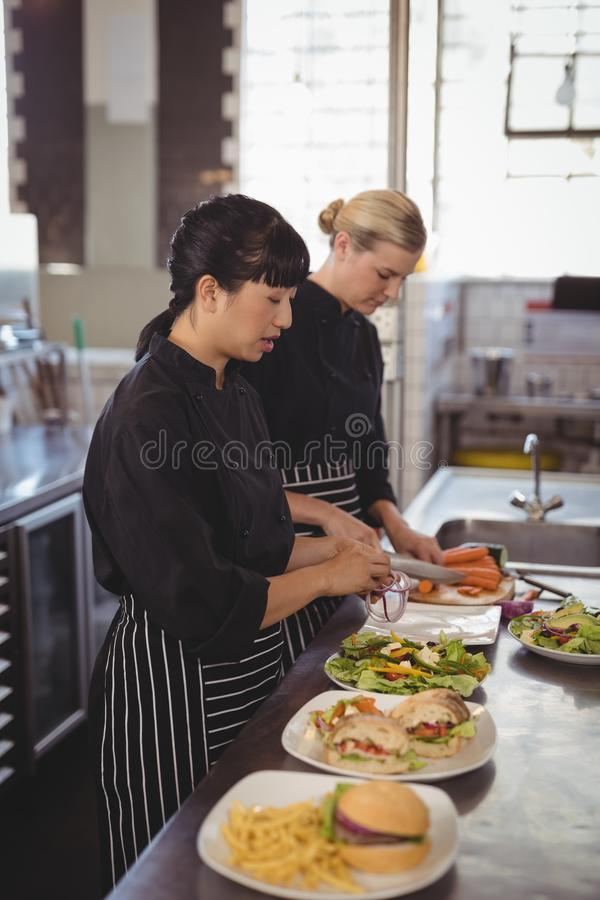 Female chefs preparing food in kitchen royalty free stock photo