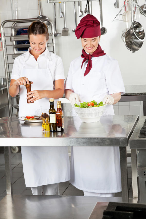 Female Chefs Preparing Food In Kitchen stock photography