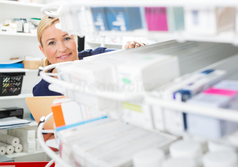 Female Chemist Counting Stock In Pharmacy stock photos