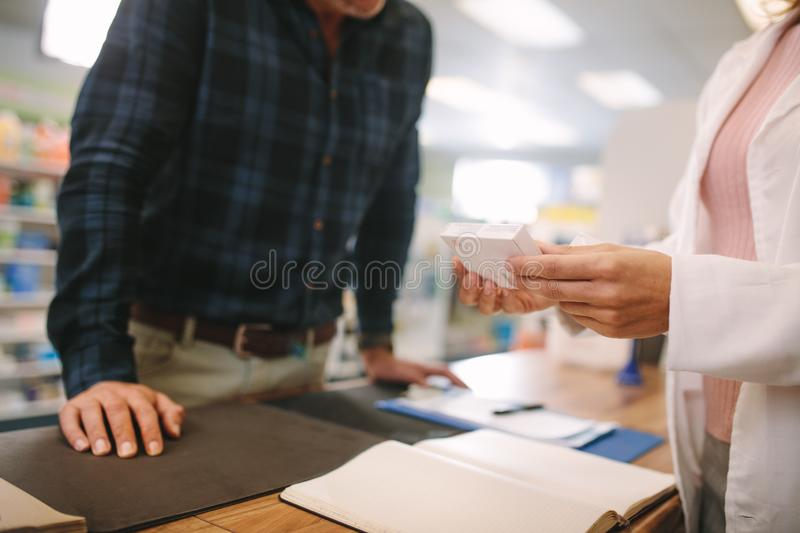 Pharmacist assisting the drug to customer in pharmacy royalty free stock image