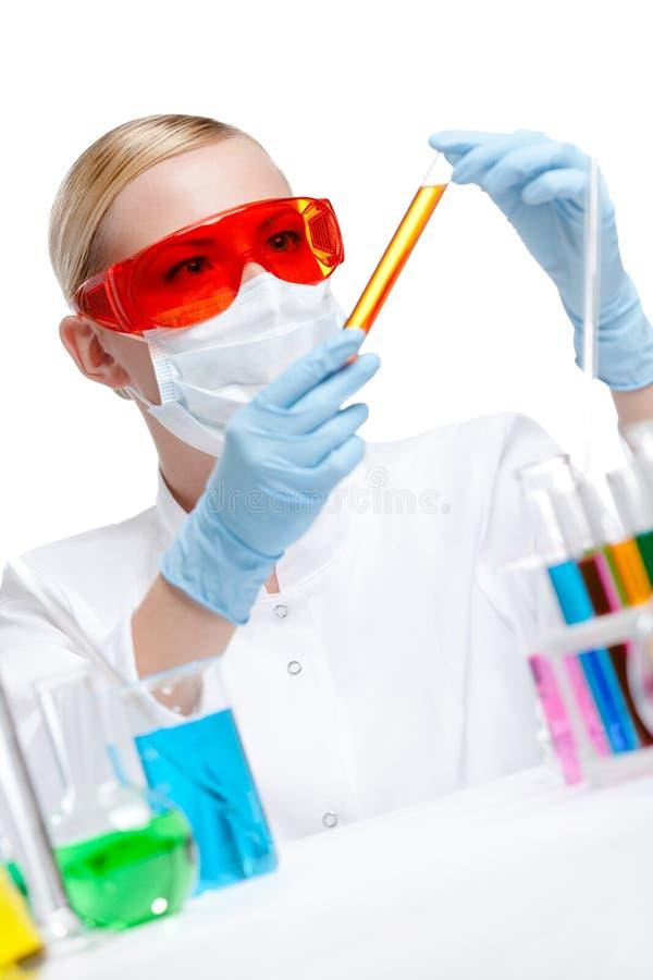 Female chemist holds a vial with orange liquid
