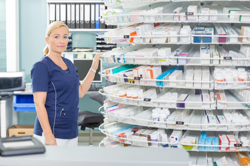 Female Chemist Standing By Shelves In Pharmacy stock photography