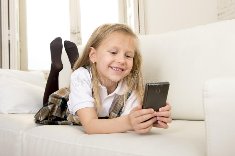 Female child with blond hair in school uniform lying on home sofa couch using internet app on mobile phone. Sweet cute and beautiful 6 or 7 years old female royalty free stock image
