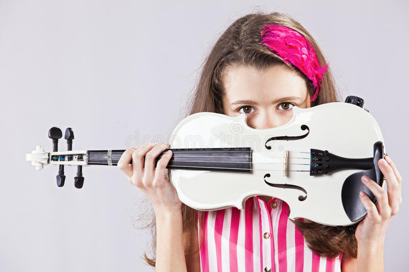 Female child playing the violin. With gray background stock photo