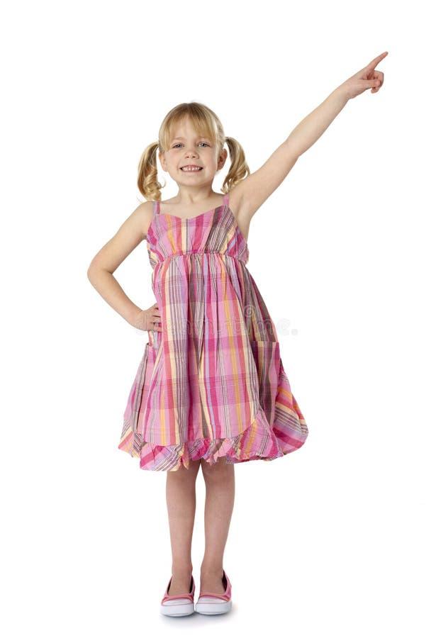 Female Child Pointing Upward. Full length studio photo of little girl pointing upward. White background stock photo
